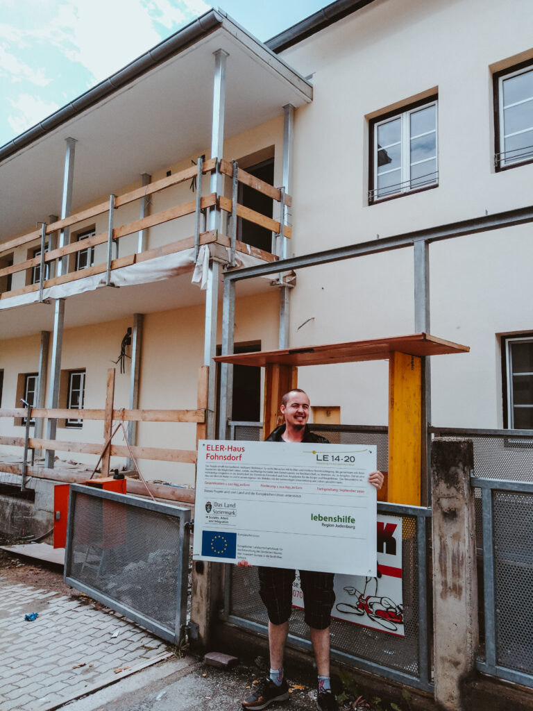 Martin Pichler vor der Baustelle mit einem Schild in der Hand