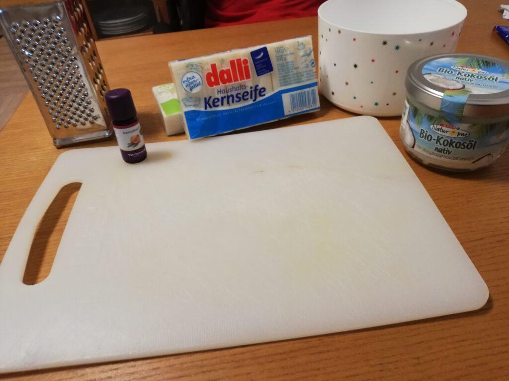 Zutaten zum Seifen-Machen aufgereiht auf einem Holztisch