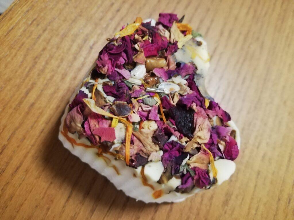 Selbstgemachte Seife in Herzform mit getrockneten Blütenblättern