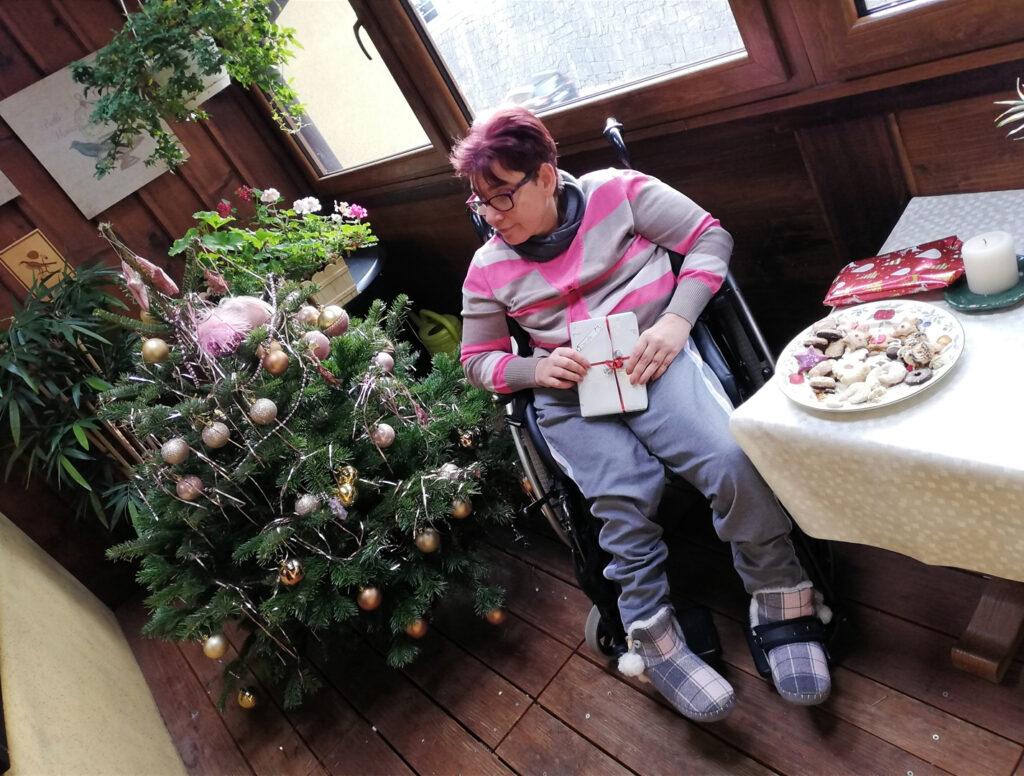 Hanna Kamrat mit Geschenk in der Hand neben einem Weihnachtsbaum